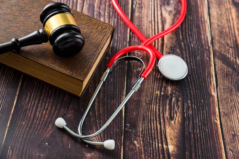 Doctor stethoscope, gavel, and law book for malpractice